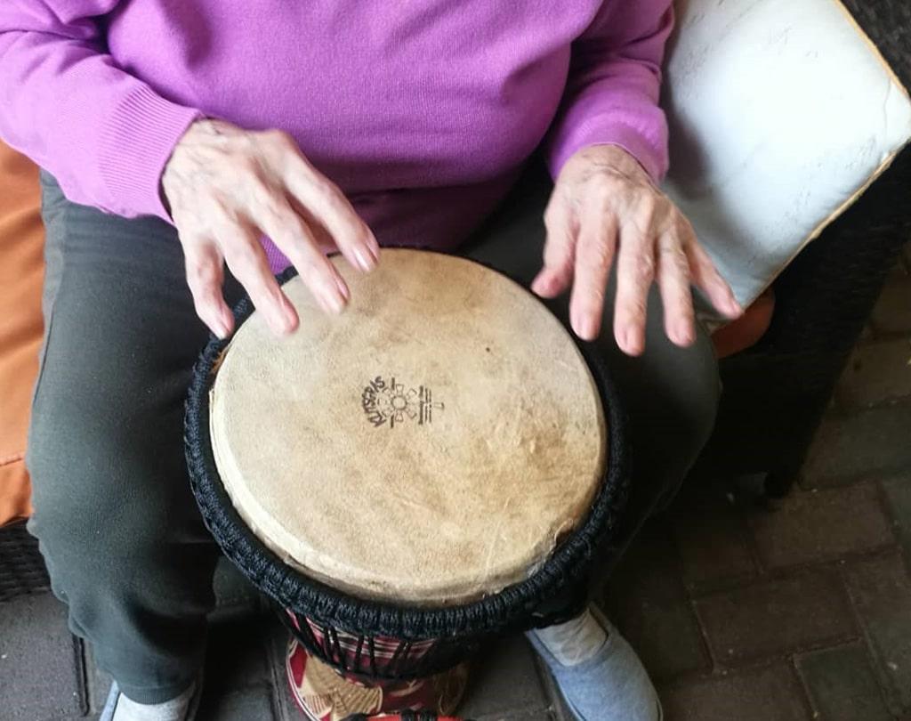 mujer mayor tocando el tambor en sesión de musicoterapia para tercera edad